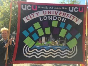 Sean, a man in his 30s, holding a pole supporting the City UCU banner. The banner shows several coloured squares surrounding a representation of London and the River Thames.